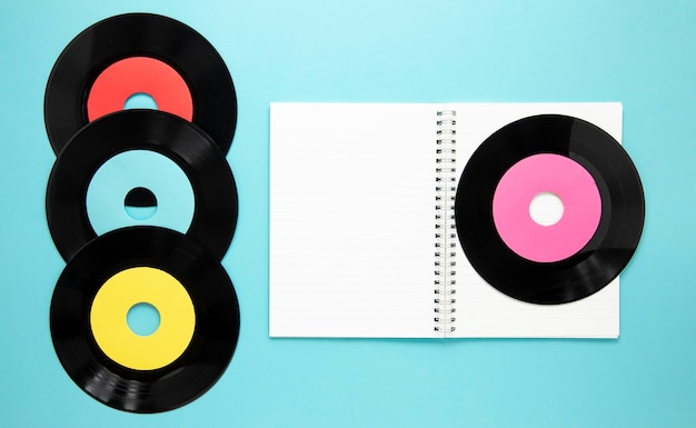 Bovenaanzicht oude vinyl schijven met notebook Gratis Foto