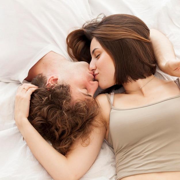 Bovenaanzicht paar kussen in bed Gratis Foto