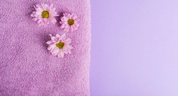 Bovenaanzicht paarse bloemen en handdoek met kopie-ruimte Gratis Foto
