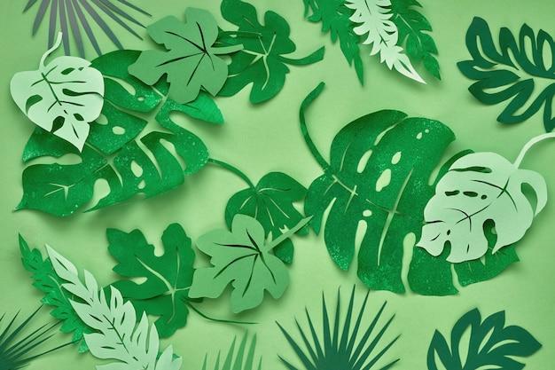 Bovenaanzicht, papier tropische bladeren op groen papier Premium Foto