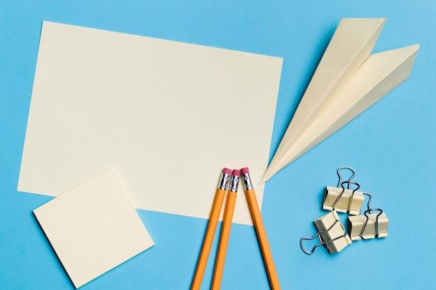 Bovenaanzicht papieren vliegtuig met potloden op het bureau Gratis Foto