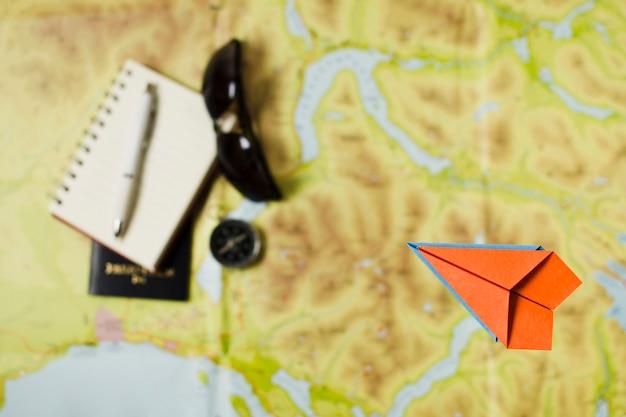 Bovenaanzicht papieren vliegtuig met reisaccessoires Gratis Foto