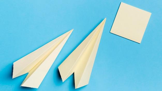Bovenaanzicht papieren vliegtuigen met plaknotities op het bureau Gratis Foto
