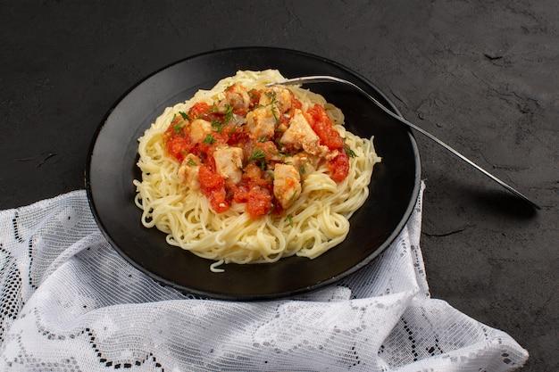 Bovenaanzicht pasta gekookt met kippenvleugels en tomatensaus in zwarte plaat o donker Gratis Foto