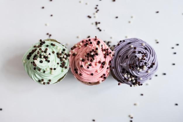 Bovenaanzicht pastel kleuren cupcakes met chocolade ballen Gratis Foto