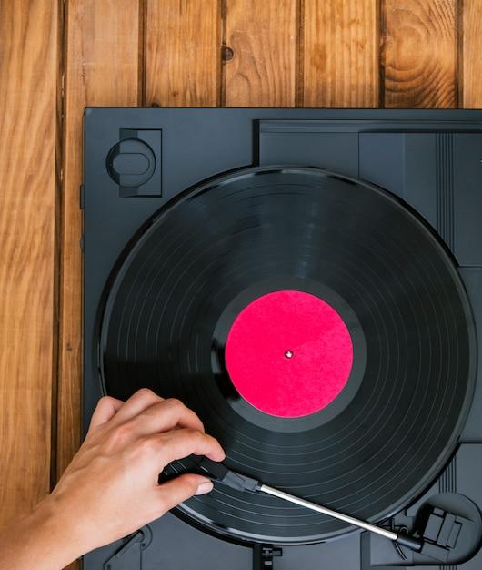 Bovenaanzicht persoon vinyl plaat in speler plaatsen Gratis Foto