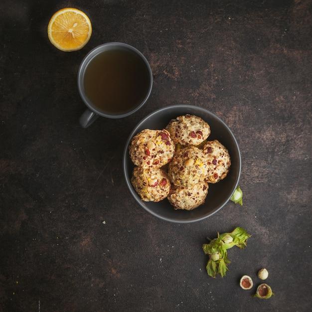 Bovenaanzicht pistache koekjes in kom met een kopje koffie en citroen diagonaal opgesteld op donkerbruin getextureerde. Gratis Foto