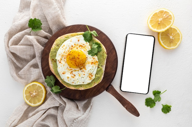 Bovenaanzicht pita met avocado-spread en gebakken ei met lege telefoon Gratis Foto