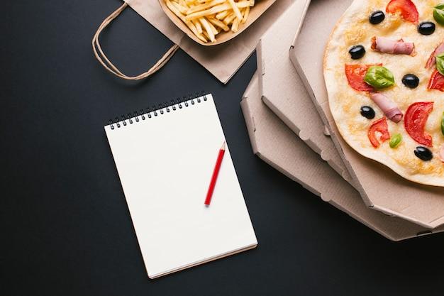 Bovenaanzicht pizza en friet met laptop Gratis Foto