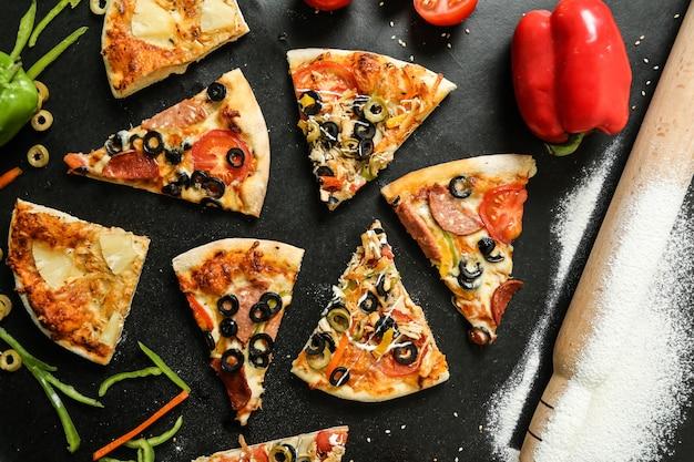 Bovenaanzicht pizza mix met tomaten, olijven en paprika op zwarte tafel Gratis Foto