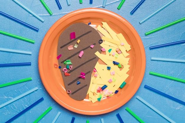 Bovenaanzicht plaat met voedsel en plastic Gratis Foto