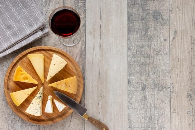 Bovenaanzicht plakjes kaas en een glas wijn Gratis Foto