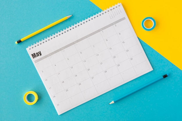 Bovenaanzicht planner agenda op gele en blauwe achtergrond Gratis Foto