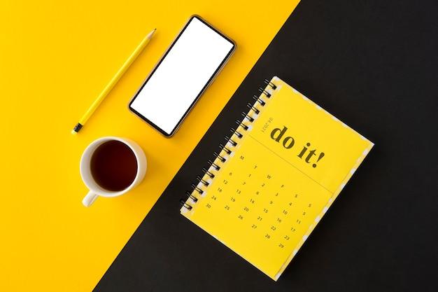 Bovenaanzicht planner gele kalender en koffie Gratis Foto