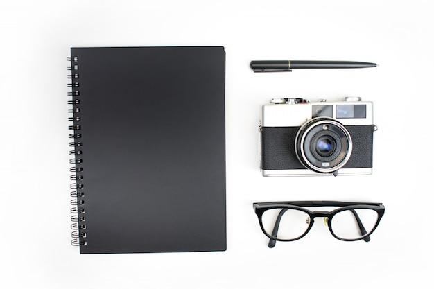 Bovenaanzicht, plat lag, zwart thema van notebooks, filmdozen, leesbril en pennen geïsoleerd Premium Foto
