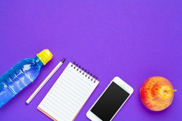 Bovenaanzicht plat leggen van kantoorbenodigdheden met waterfles achtergrond Premium Foto