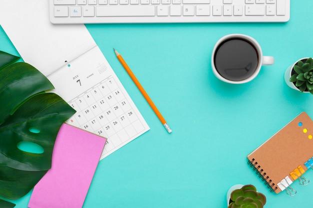 Bovenaanzicht plat leggen van werkruimte bureau stijl ontwerp kantoorbenodigdheden met kalender Premium Foto