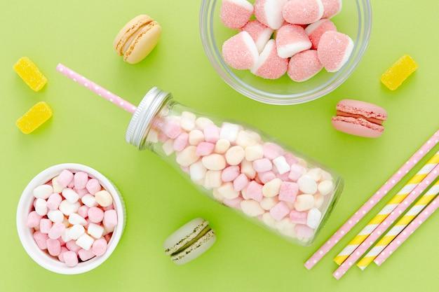 Bovenaanzicht pot met snoep en macarons Gratis Foto