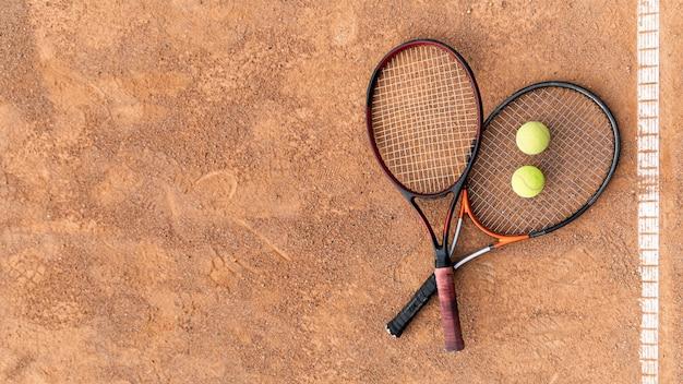 Bovenaanzicht rackets met tennisballen op grond Gratis Foto