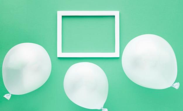 Bovenaanzicht regeling met ballonnen op groene achtergrond Gratis Foto