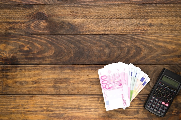 Bovenaanzicht regeling met bankbiljetten en zakrekenmachine Gratis Foto
