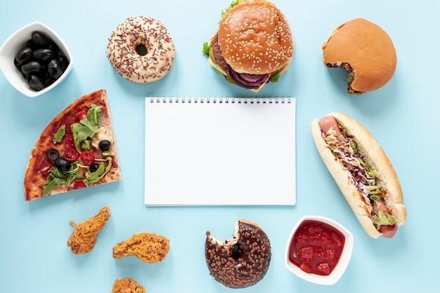 Bovenaanzicht regeling met fast food en laptop Gratis Foto