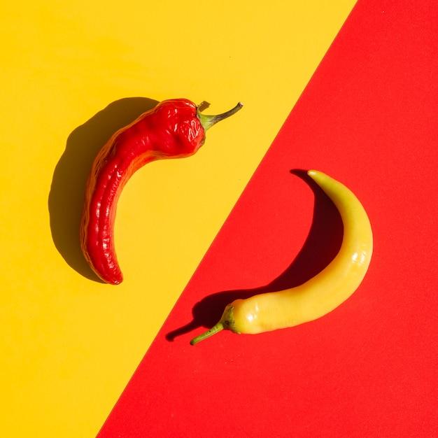 Bovenaanzicht regeling met pittige pepers en gele achtergrond Gratis Foto