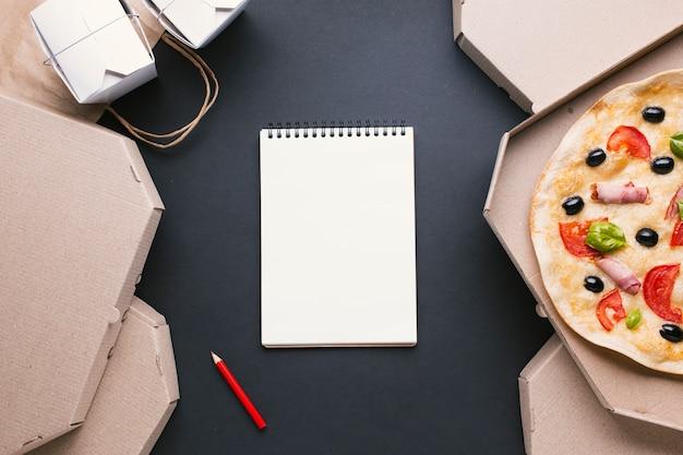 Bovenaanzicht regeling met pizzadozen en notitieboekje Gratis Foto
