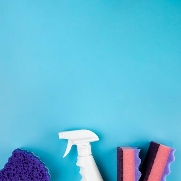 Bovenaanzicht regeling met schoonmaakmiddelen op blauwe achtergrond Gratis Foto