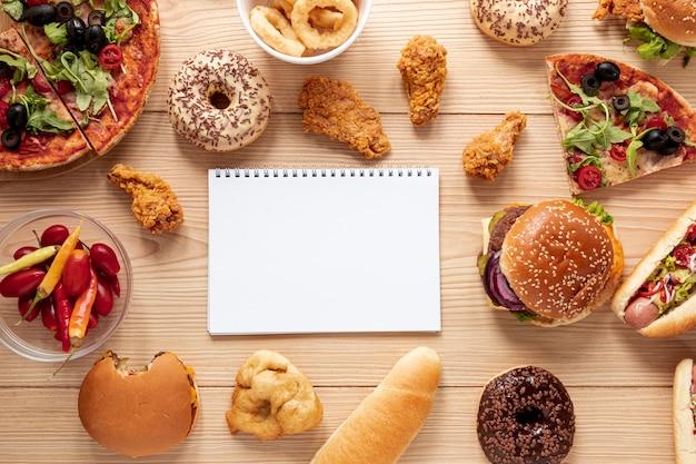 Bovenaanzicht regeling met voedsel en laptop Gratis Foto