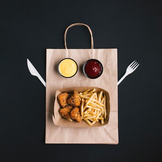 Bovenaanzicht regeling met voedsel op papieren zak Gratis Foto