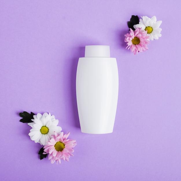 Bovenaanzicht regeling met witte fles en bloemen Gratis Foto