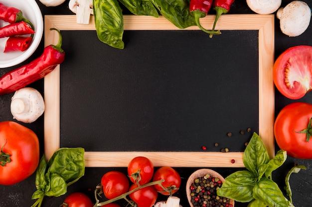 Bovenaanzicht regeling van groenten met leeg bord Gratis Foto
