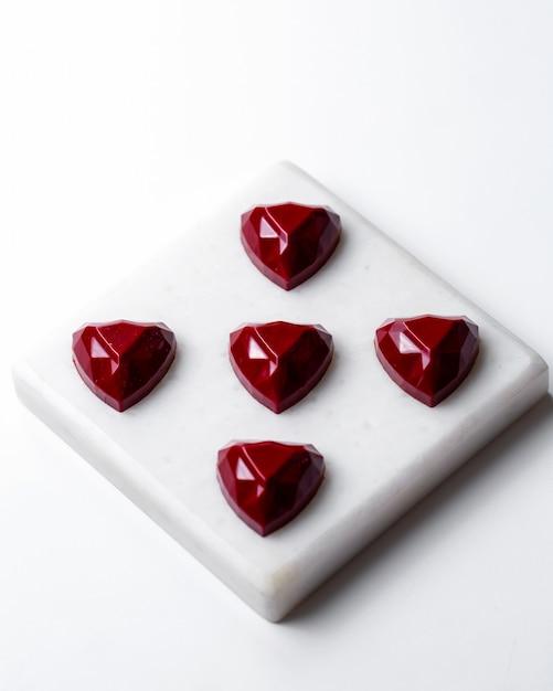 Bovenaanzicht rode chocolade hartvormige snoepjes op witte stand Gratis Foto