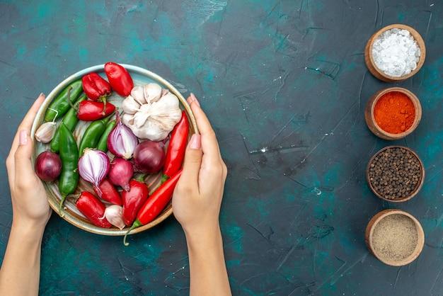 Bovenaanzicht rode paprika met uien knoflook samen met kruiden op de donkere achtergrond maaltijd groente salade ingrediënt Gratis Foto