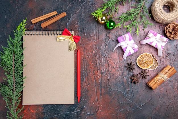 Bovenaanzicht rode pen een notebook pijnboomtakken kerstboom ballen stro draad kaneel steranijs kerstcadeaus op donkerrood oppervlak Gratis Foto