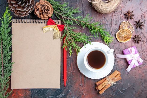 Bovenaanzicht rode pen een notitieboekje pijnboomtakken kerstboom bal speelgoed en geschenken een kopje thee witte schotel kaneelstokjes anijs op donkerrood oppervlak Gratis Foto