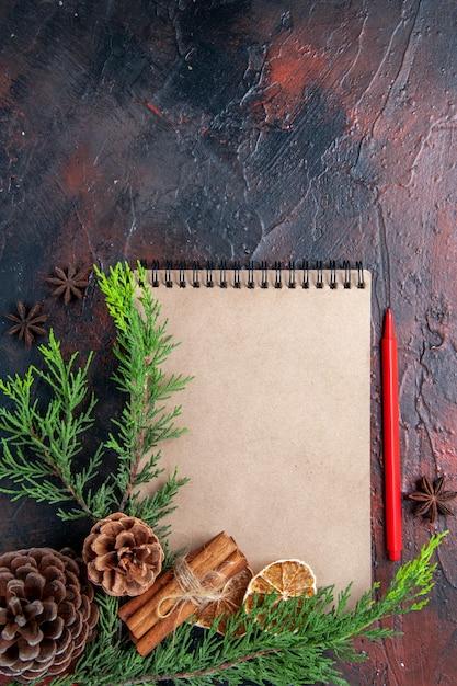 Bovenaanzicht rode pen een notitieboekje pijnboomtakken steranijs gedroogde schijfjes citroen op donkerrood oppervlak kopie ruimte Gratis Foto