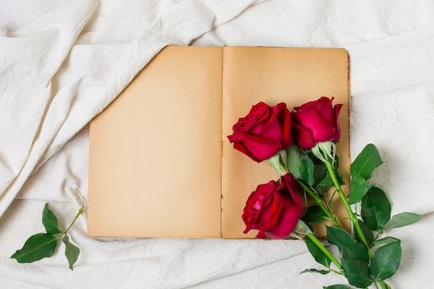 Bovenaanzicht rode rozen bovenop een boek Gratis Foto