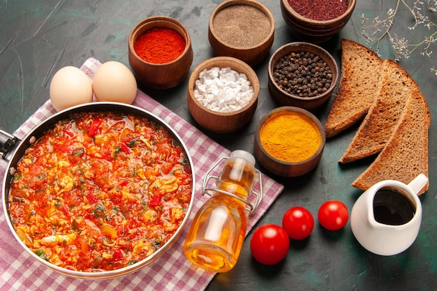 Bovenaanzicht roerei met tomaten en verschillende kruiden op de donkergroene achtergrond Gratis Foto