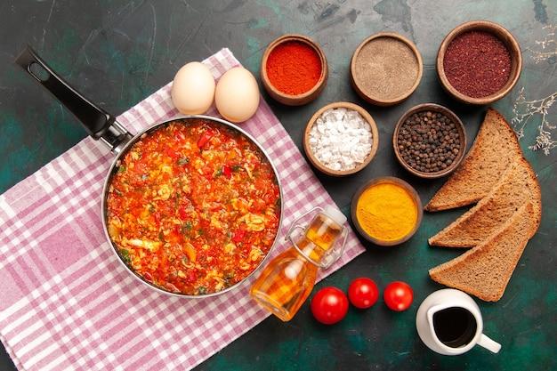 Bovenaanzicht roerei met tomaten en verschillende kruiden op het donkergroene bureau Gratis Foto