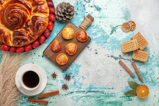 Bovenaanzicht ronde heerlijke taart met aardbeienwafels en kopje thee op lichtblauw oppervlak Gratis Foto