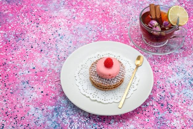 Bovenaanzicht ronde koekje met franse macarons en thee op de gekleurde backgorund suiker zoete cake kleur Gratis Foto
