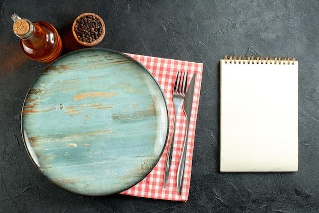 Bovenaanzicht ronde schotel diner mes en vork op rood en wit geruit servet notebook op zwarte tafel Gratis Foto