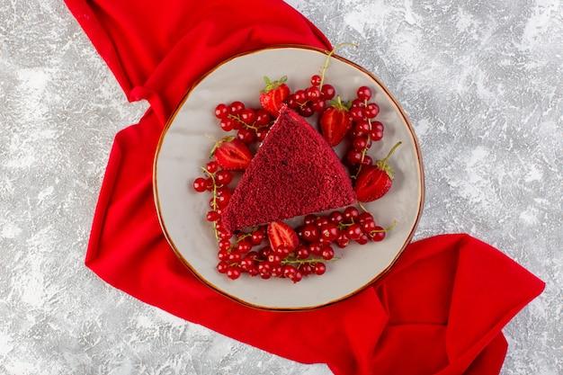 Bovenaanzicht rood cake stuk fruitcake stuk binnen plaat met verse veenbessen en aardbeien op de grijze bureau cake zoete koekjesthee Gratis Foto