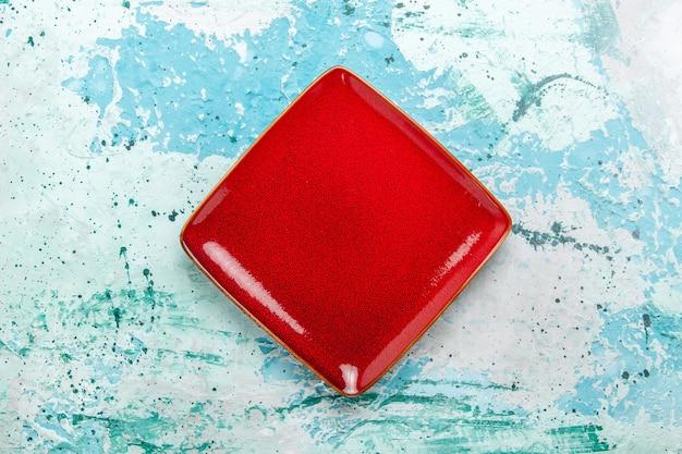 Bovenaanzicht rood plaat vierkant gevormd leeg op lichtblauwe achtergrond Gratis Foto