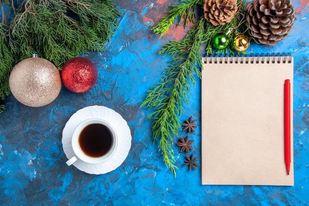 Bovenaanzicht rood potlood op een notebook pijnboomtakken xmas ornamenten een kopje thee op blauwe ondergrond Gratis Foto