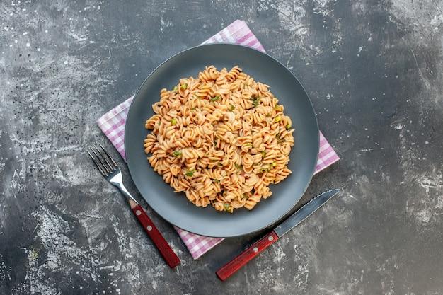 Bovenaanzicht rotini pasta op ronde plaat op roze wit geruit servetmes en vork op grijze tafel Gratis Foto