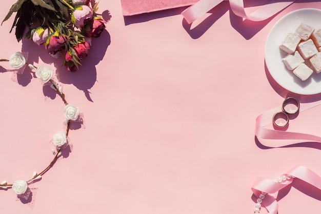 Bovenaanzicht roze bruiloft arrangement met roze achtergrond Gratis Foto