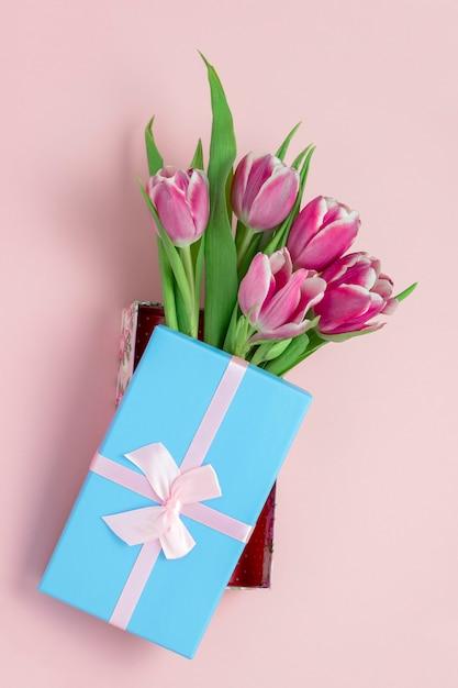 Bovenaanzicht roze tulpen in een blauwe doos met roze satijnen strik op een pastel roze Premium Foto